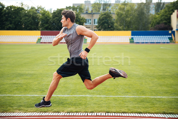 Side view of a sprinter running on athletics tracks Stock photo © deandrobot