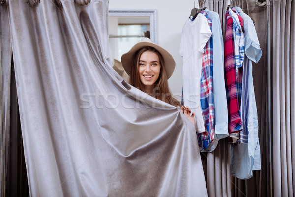 Cheerful young woman covered herself standing in fitting room Stock photo © deandrobot