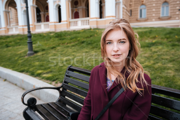 Cute lovely young woman sitting on bench outdoors Stock photo © deandrobot