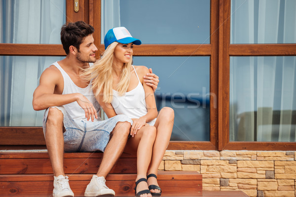 Young beautiful couple sitting on house steps outdoors Stock photo © deandrobot