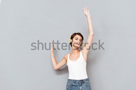 Woman listening music in headphones with raised hands up Stock photo © deandrobot