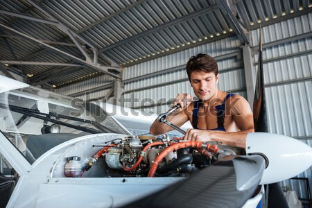 Happy aircraft mechanic standing with arms crossed near small airplane Stock photo © deandrobot