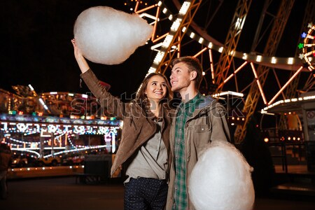 Couple holding cotton candy and embracing in amusment park Stock photo © deandrobot