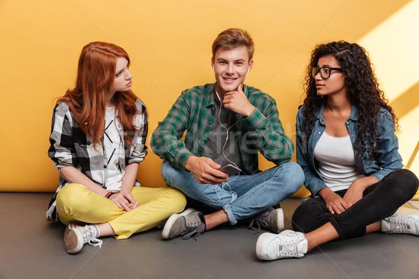 Vrolijk man vergadering twee meisjes luisteren naar muziek Stockfoto © deandrobot
