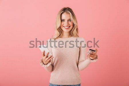 Smiling young woman holding opened book and looking at camera Stock photo © deandrobot