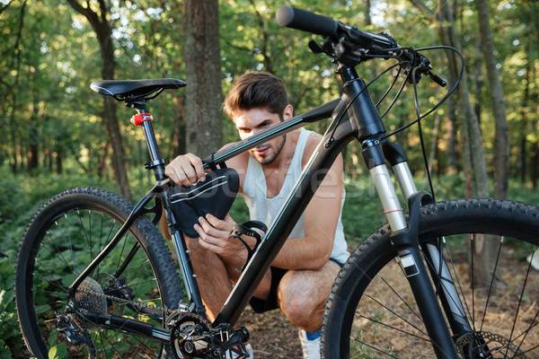 Man repairing a bicycle in forest Stock photo © deandrobot