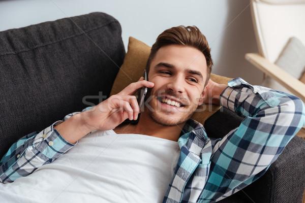 Nevet sörte férfi hazugságok kanapé beszél Stock fotó © deandrobot