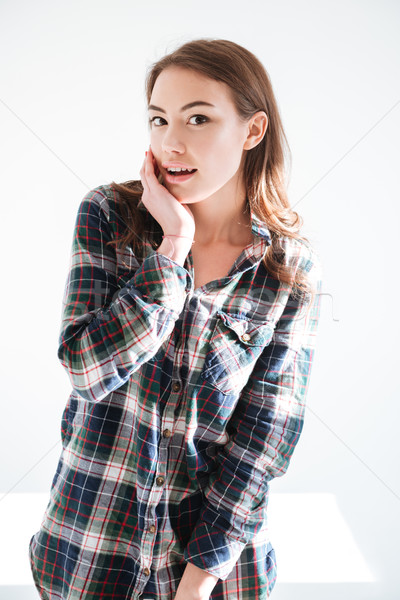 Happy surprised young woman in plaid shirt Stock photo © deandrobot