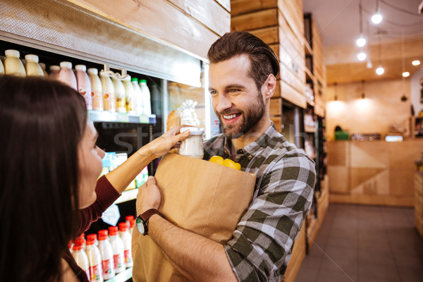 Couple with packet of food in grossery shop Stock photo © deandrobot