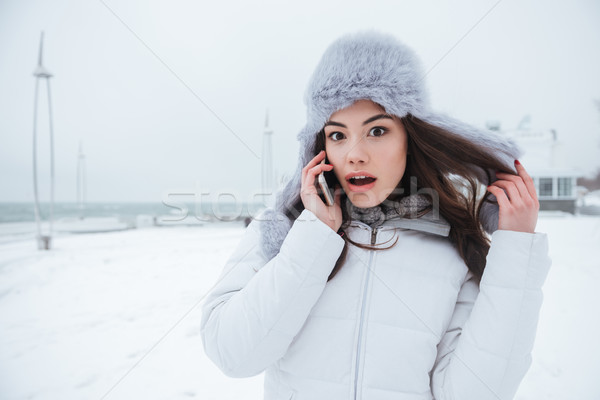 Shocked young lady wearing hat talking by her phone. Stock photo © deandrobot