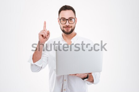 Stock photo: Concentrated young bearded man using laptop and pointing
