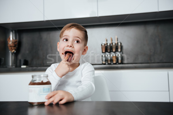 Little boy eating sweeties at kitchen Stock photo © deandrobot