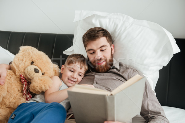 Boy lies near toy with his bearded father reading book. Stock photo © deandrobot