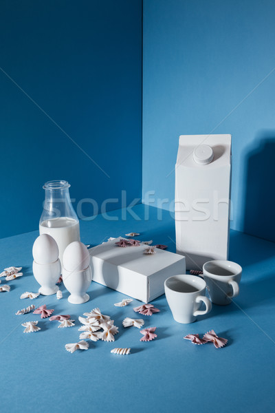 Two blank boxes,, milk bottle, white coffee cups and pasta Stock photo © deandrobot