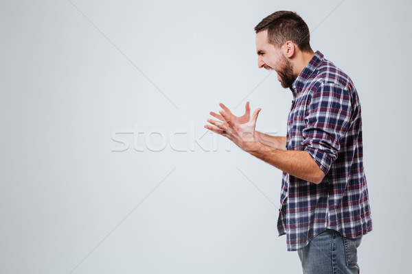 Side view of Screaming Bearded man in shirt Stock photo © deandrobot