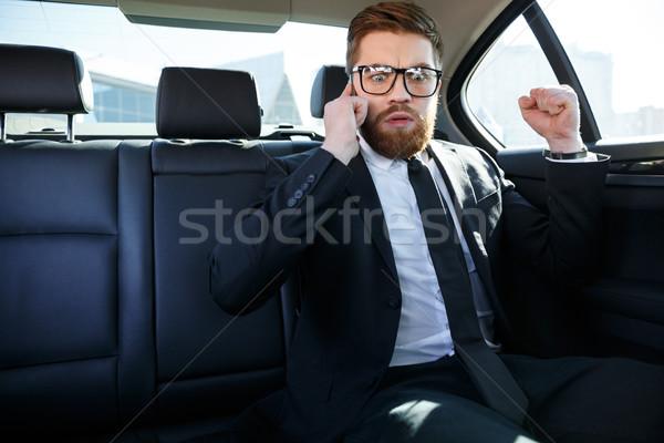 Decepcionado barbado hombre de negocios hablar teléfono móvil Foto stock © deandrobot