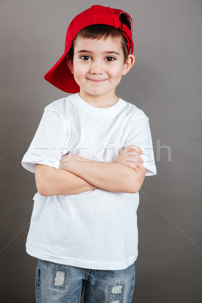 Happy little boy in red cap standing with arms crossed Stock photo © deandrobot