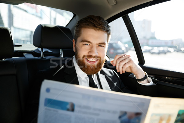 Smiling business man with newspaper Stock photo © deandrobot