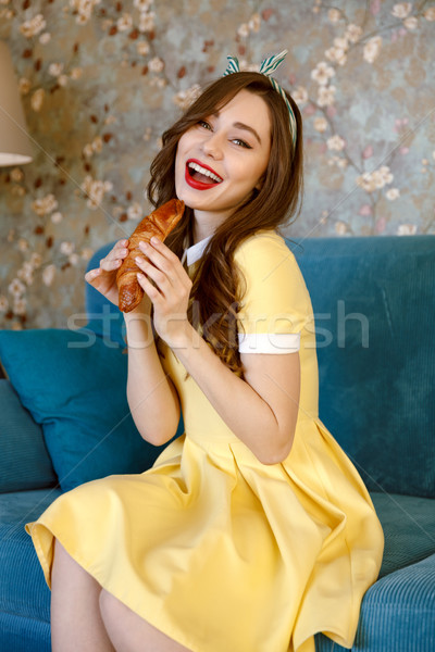 Feliz jóvenes pinup dama comer croissant Foto stock © deandrobot