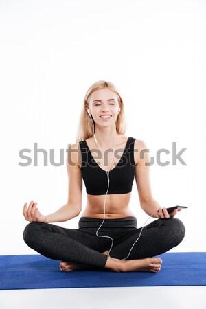 Cheerful fitness woman sitting make yoga exercises listening music Stock photo © deandrobot