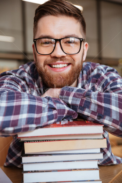 Smiling male student resting on stack of books Stock photo © deandrobot