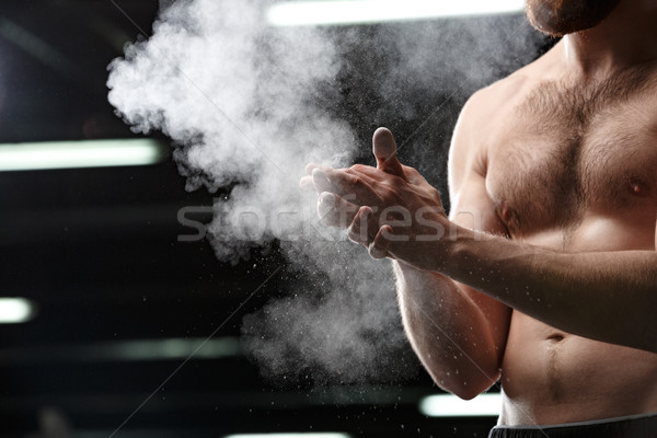 Handsome sports man in gym rubbing hands with chalk Stock photo © deandrobot
