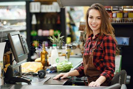 Happy cashier woman on workspace in supermarket shop. Stock photo © deandrobot