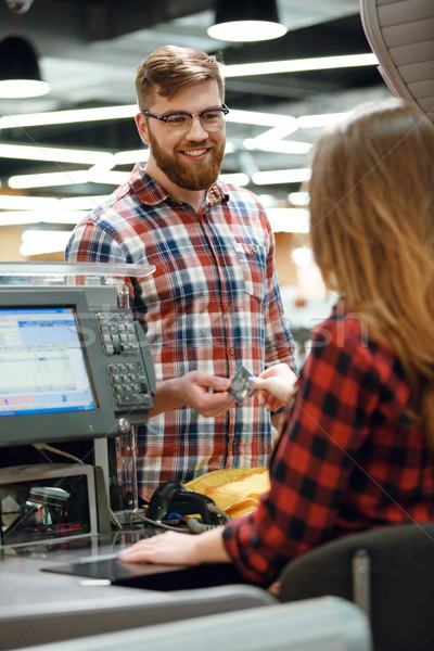 Man standing near cashier's desk in supermarket shop Stock photo © deandrobot