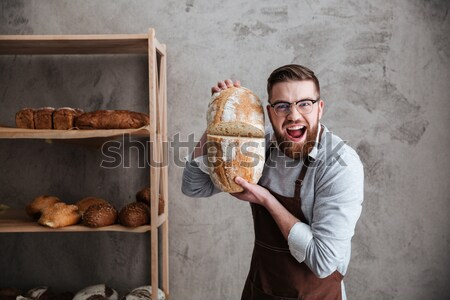 Screaming man baker standing with paper bag on head Stock photo © deandrobot