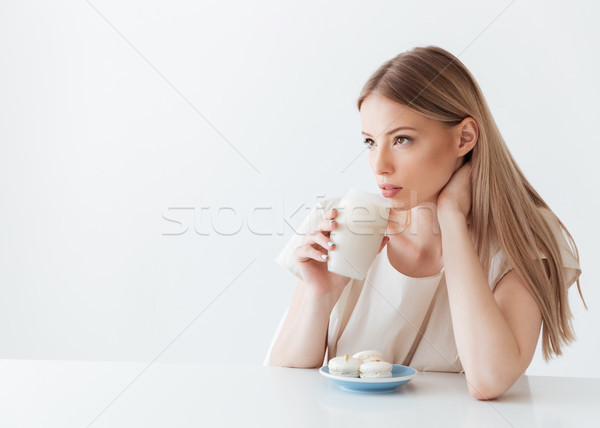 Lady sitting isolated near sweeties drinking coffee Stock photo © deandrobot