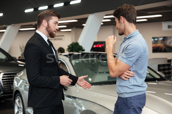 Handsome young car salesman showing a new car Stock photo © deandrobot