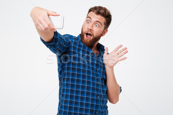 Surprised bearded man in shirt making selfie on his smartphone Stock photo © deandrobot