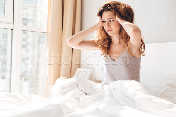 Sad lady lies in bed indoors. Looking aside. Stock photo © deandrobot