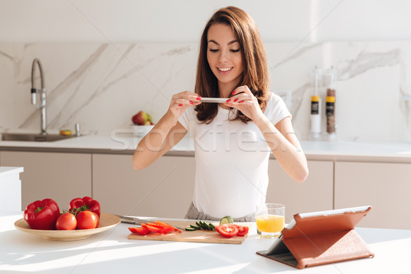 Smiling casual woman taking a picture of sliced vegetables Stock photo © deandrobot