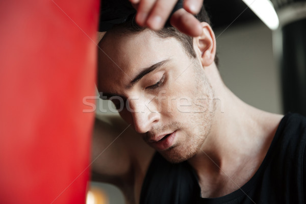 Portrait of tired boxer near punching bag Stock photo © deandrobot