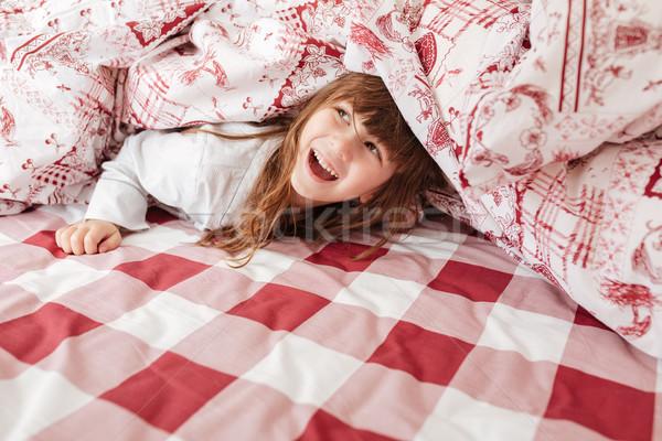 Happy child on bed under blanket Stock photo © deandrobot