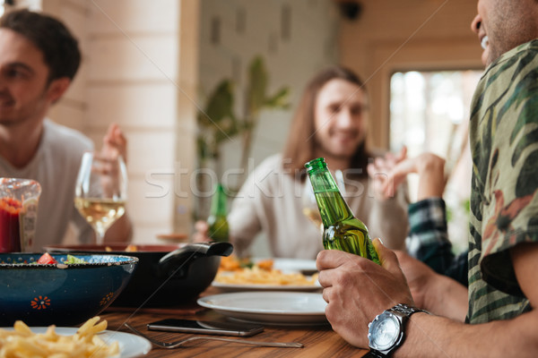 Group of men talking and drinking beer at the table Stock photo © deandrobot