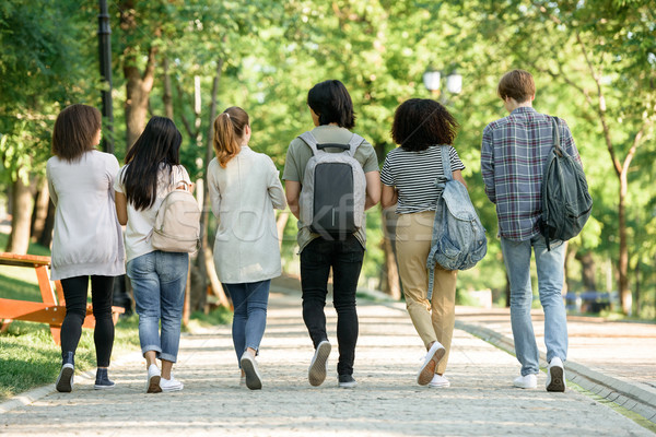 Back view image of multiethnic group of young students Stock photo © deandrobot