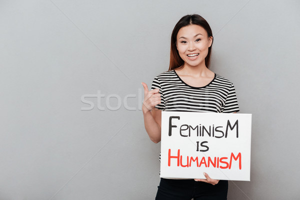 Happy woman holding blank with text about feminism. Stock photo © deandrobot
