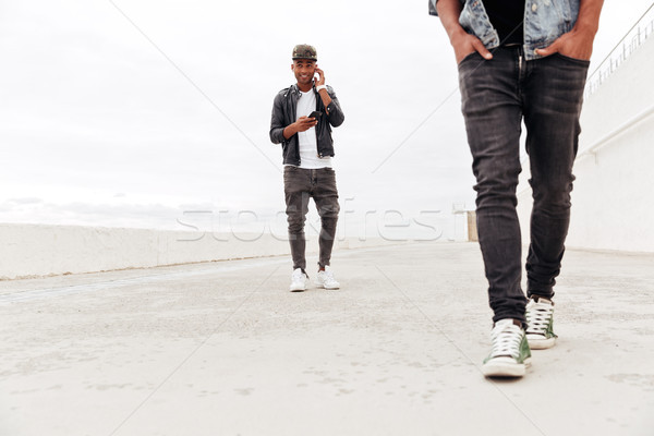 Man looking aside using phone and listening music. Stock photo © deandrobot