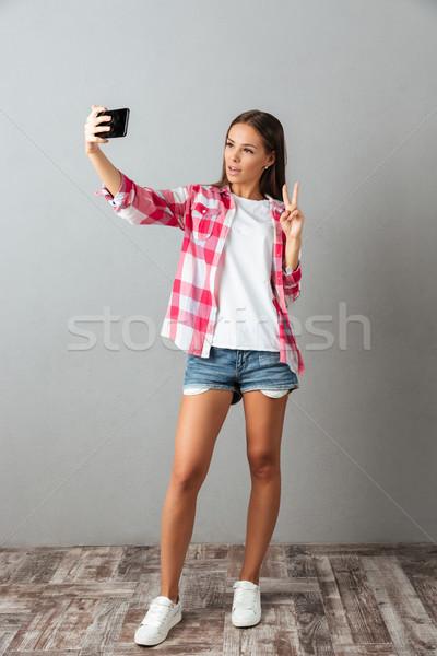 Photo jeunes belle femme smartphone gris Photo stock © deandrobot