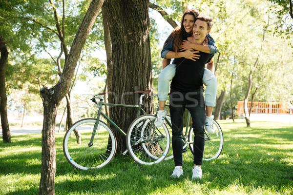 Beautiful cheerful couple enjoying piggyback ride Stock photo © deandrobot