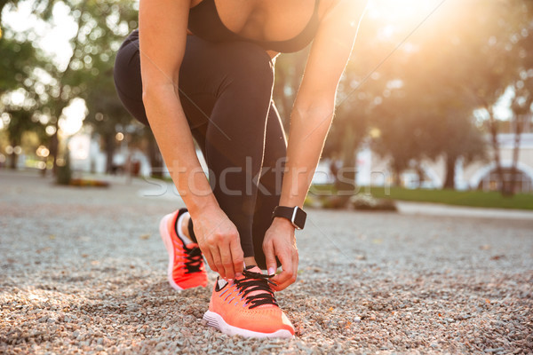 Cropped photo of strong young sports woman tie laces. Stock photo © deandrobot