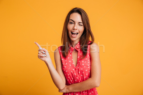 Boldog barna hajú nő ruha mutat felfelé Stock fotó © deandrobot