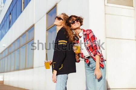 Twee gelukkig tienermeisjes zonnebril drinken sinaasappelsap Stockfoto © deandrobot