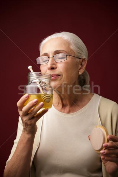 Serious woman over dark blue background holding honey Stock photo © deandrobot