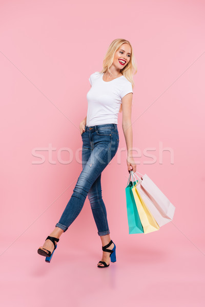 Full-length image of happy carefree blonde woman walking with packages Stock photo © deandrobot
