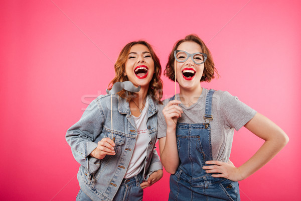 Funny women friends holding fake moustache and glasses. Stock photo © deandrobot