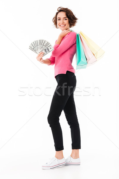 Smiling young lady standing isolated with shopping bags and money. Stock photo © deandrobot