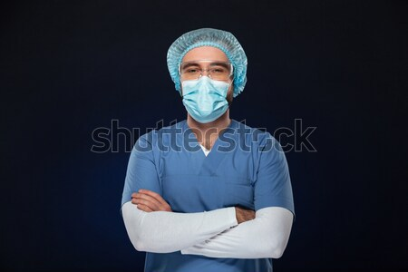 Young doctor in medical mask and cap looking camera Stock photo © deandrobot